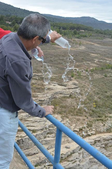 Uno de los participantes en la marcha vierte agua en el Pantano de Entrepeñas