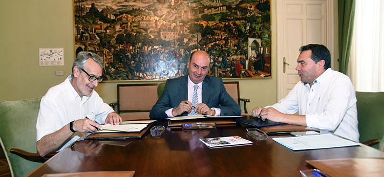 Latre y Muñoz wen la firma del Convenio con Cáritas