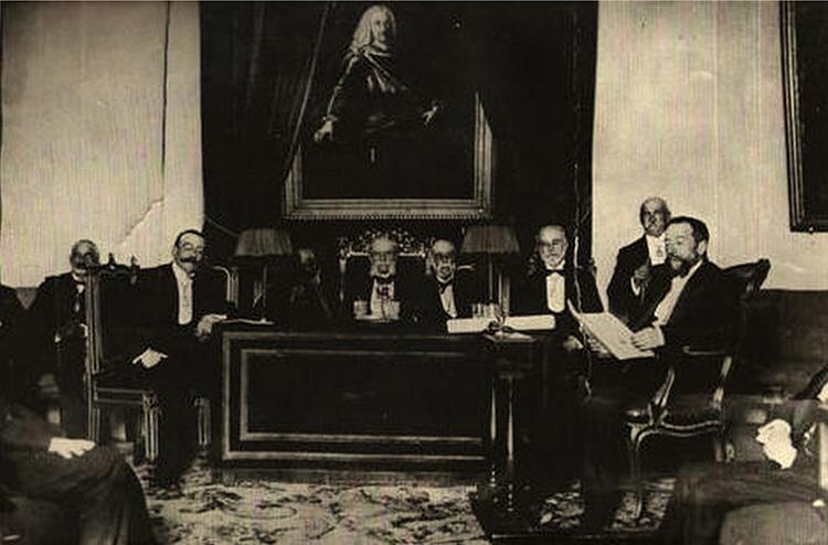 Manuel Pérez Villamil en la lectura de su discurso de ingreso en la Real Academia, frente a él, Juan Catalina García