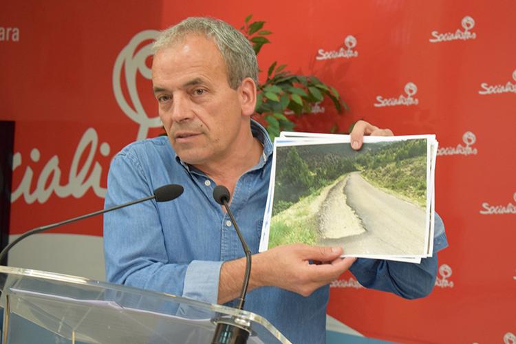 Julio García muestra una foto con el estado actual de la carretera GU-958