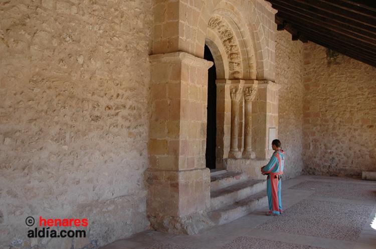 La botarga de Beleña de Sorbe delante de la portada de la iglesia románica